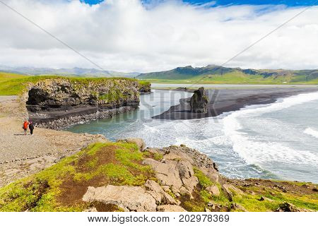 Augustu 2015 north coast of dyrholaey promontory  vestur skaftafellssysla iceland . two tourists admire the landscape from above the promontory