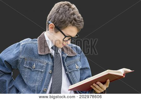 Stylish preteen boy reading book with smart interested expression black glasses tie denim jacket. Education success and learning concept. Isolated on dark gray.