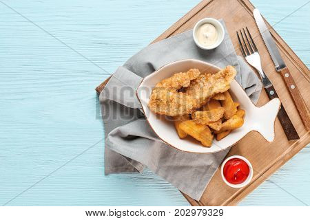 Plate with fried fish and chips on wooden board