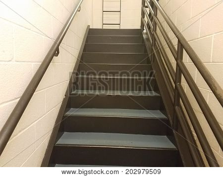 cement stairs in a stairwell with metal railing and white walls with ladder