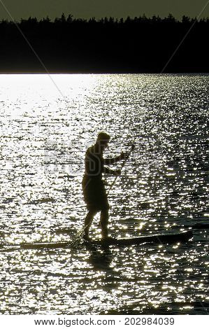 Closeup Of A Silhouetted Man Paddle Boarding On A Saskatchewan Lake