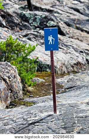 A blue hiking trail sign over rough rocks.