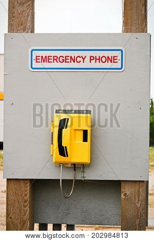 An Emergency Phone Located On A Wooden Billboard