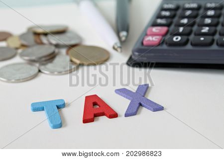 Business, finance, saving money, investment, taxes or accounting concept : Wooden word TAX, coins and calculator on office desk table