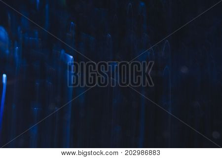 Abstract background of blue bends in motion on black. Bokeh of defocused curves, blurred neon leds, similar to rain drops, backdrop of magic nature around