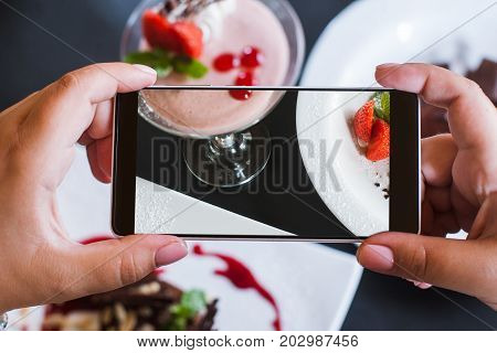 Food photos of delicious desserts by smartphone in restaurant. Creamy strawberry souffle, photoshoot and new technology, close up pov picture