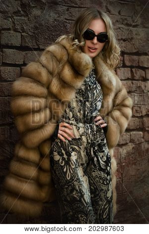 The woman in a fur coat. A coat from arctic fox in front of Brick wall