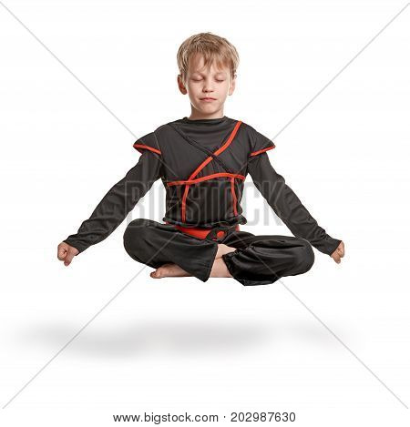 Little relaxed ninja meditating in levitation. lotus pose on white background