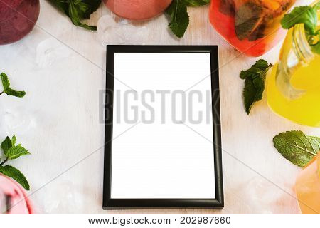 Picture frame laying on table with partially seen fruit drinks around. Food blogs, menu and recipes for web sites of cafe and restaurant, close up picture with copy space