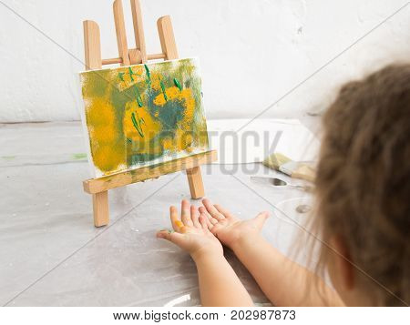 Little artist in art studio. Abstract painting. Early childhood education, interesting hobby for children, unrecognizable child, drawing concept