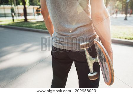 Unrecognizable young man with skateboard in hands. Waiting for next step of sport challenge and competition, short break and self-confidence. Skateboarding urban lifestyle and culture background