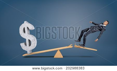 A big concrete dollar sign rests on a wooden seesaw against a businessman falling from a broken plank. Business and profit. Loss and acquisition. Forex and money exchange.