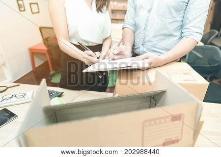 Young entrepreneur checking document with marketing team at home office. Conceptual for small businesses starting own company and online marketing.