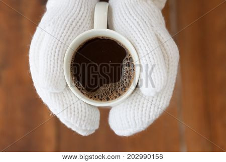 coffee mug in hands mittens outdoor in the winter on Christmas Eve