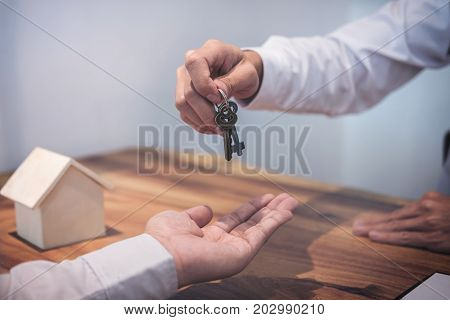 Broker agent's hand holding House key in insurance giving to buyer customer real estate agent.