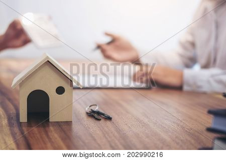 Man sign a home insurance policy on home loans Agent agent holds loan investment chart graph documents and calculating table installment payment Real Estate concept.