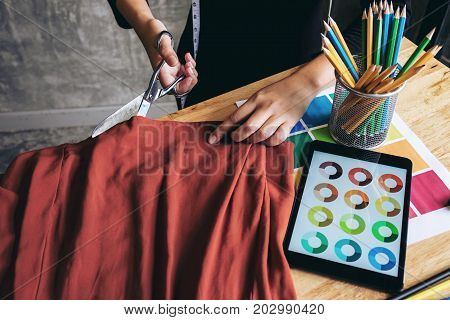 Young woman dressmaker or designer working as fashion designers measure and Cutting for clothes profession and job occupation Fashion Designer Stylish Concept.