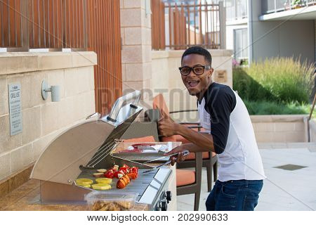 Closeup portrait handsome young guy with big glasses barbecuing yummy food isolated outside background