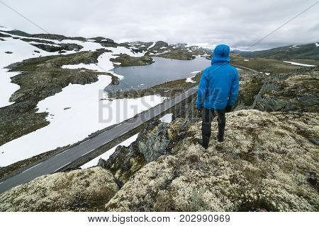 Norwegian Tourist Route Aurlandsfjellet runs from Aurlandsvangen to Laerdalsoyri. Bjorgavegen - mountain road in Norway. A guy is standing on a hill and looking at the lake