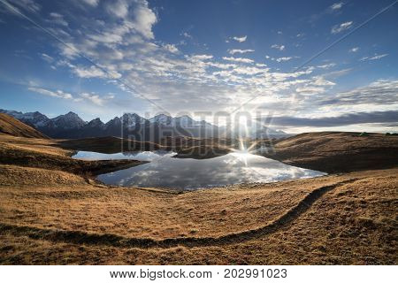 Koruldi - mountain lake. Sunny morning with blue sky. Beautiful sun rays. Caucasus, Georgia, Zemo Svaneti