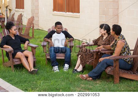 Closeup portrait family sitting down outside on patio having joyful conversation isolated outdoors background