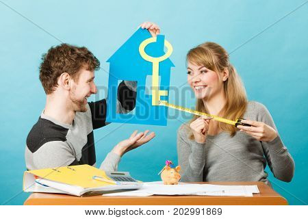 Real estate ownership finance concept. Just married designing their house. Young couple man and woman holding cutouts of key and home.