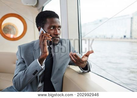 Confident banker or rich man speaking by smartphone while traveling by steamship