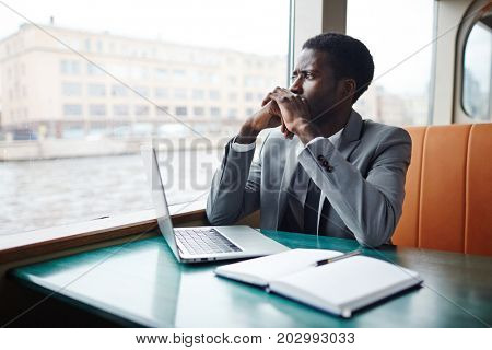 Young analyst in suit thinking of new ideas for financial project while traveling by ship