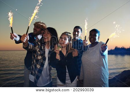 Group of ecstatic friends with fire-crackers having fun by seaside in summer night