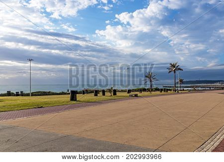 Coastal landscape empty paved promenade against sea the Bluff and blue cloudy sky on Golden Mile Beachfront in Durban South Africa