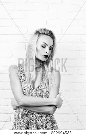 girl or beautiful woman cute fashion model with sexi makeup and blond hair in sexy undershirt on white brick wall black and white