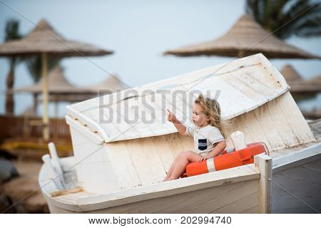 Child little boy little sitting in life buoy on boat. Small kid pointing with pointer finger at beach. Marine safety and transport. Childhood and baby care concept. Travel and summer vacation.