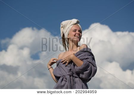 Model with naked shoulders sunbathing on sunny day. Spa and wellness. Summer vacation concept. Happy woman in bathrobe and towel on head. Girl smiling on cloudy blue sky.