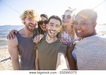 Ecstatic friends enjoying their rest on the beach and making selfie