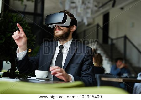 Young specialist having visionary experience at coffee break in cafe