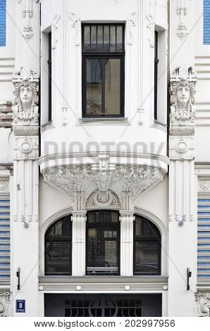 Riga, Latvia - December 27, 2014: Front facade of old building with sculptures of human heads in Art Nouveau style (Jugendstil) and bay windows.