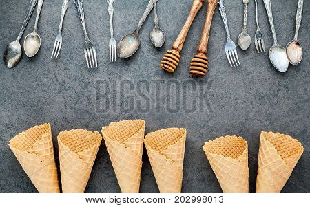 Flat Lay Ice Cream Cones Collection , Spoons ,fork And Honey Dipper On Dark Stone Background . Blank