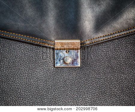 Texture of a black portfolio with a lock of genuine leather with embossed close-up texture for a designer background with space for text.