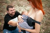 Happy young mother stands and breastfeed newborn baby on walk father sits next to them. poster
