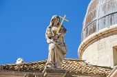 Statue of personifications of Faith on top of the facade of the baroque Church of St. Blaise in the old city of Dubrovnik. poster