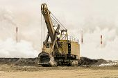 Big bucket mining excavator on a crawler track against a background of dense factory smog and fog with smoking chimneys. Heavy industry background. Excavator with mechanical drive and flexible suspension of work equipment. poster