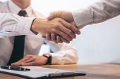 Real estate broker agent and customer shaking hands after signing contract documents for realty purchase Bank employees congratulate Concept mortgage loan approval. poster