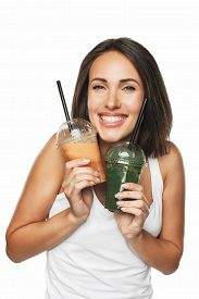 Young attractive brunette woman holding takeaway cups with smoothie. Healthy eating concept. Isolated on white.