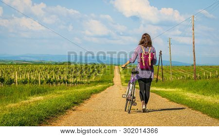 Traveler Girl Walking Through Fields. Young Girl Traveler Walking In Nature. Traveler With Backpack