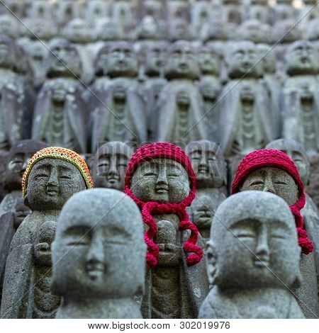 poster of Rows of stone Buddhas. Many stone sculptures of the Buddha in red knitted hats. Buddha figures of Hase-Dera Temple in Kamakura, Japan. Jizo statues at Jizo-Do