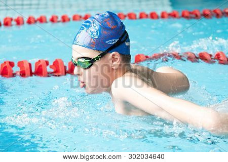 Khabarovsk, Russia - May, 19, 2019: Children Swimming Butterfly. Indoor Swimming Pool With Clear Blu