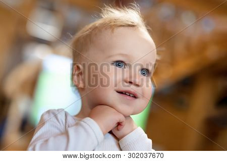 Cute Caucasian Blond Toddler Boy Pleasantly Surprised Looking Somewhere Indoors. Adorable Little Chi