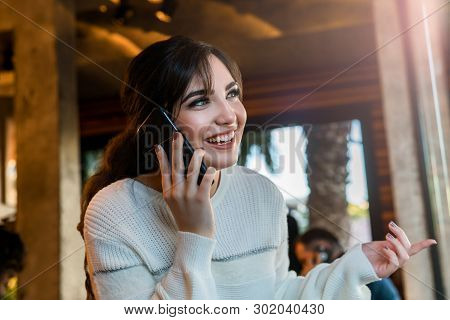 Happy Young Woman Talking On Cell Phone While Sitting Alone In Coffee Shop. Smiling Girl Has Telepho