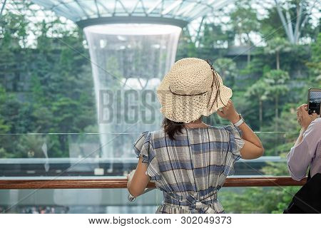 Young Woman Wear Blue Dress And Hat, Asian Traveler Standing And Looking To Beautiful Rain Vortex At