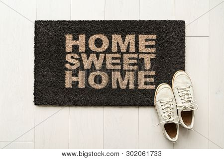 Home sweet home door mat at house entrance with women's sneakers of woman that has just arrived moved in. New condo. poster
